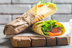 Fresh tortilla wrap. With vegetables and salmon on paper Stock Image