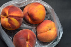 Fresh tree ripened peaches in plastic grocery store produce bag Royalty Free Stock Image
