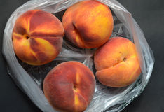 Fresh tree ripened peaches in plastic grocery store produce bag Royalty Free Stock Photography