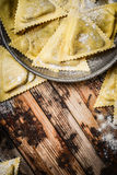 Fresh triangular ravioli in metal bowl on rustic wooden background, top view. Close up Stock Images