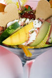 Fresh tropical fruit with cream or ice cream Stock Images