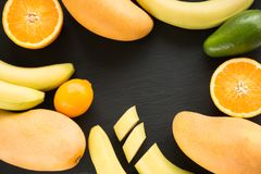 Fresh tropical fruit, mango , banana, orange, lemon, avocado around on black slate dish. View from above. Royalty Free Stock Photo