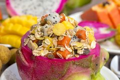Fresh tropical fruit salad with oat flakes, raisins, nuts and honey in dragon fruit skin, close up. Fresh tropical fruit salad with oat flakes, raisins, nuts and Stock Images