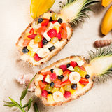 Fresh tropical fruit salad served outdoors. In halved hollowed out pineapples during a summer vacation at a seaside resort Royalty Free Stock Photos