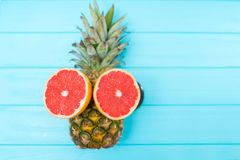 Fresh tropical fruit still life with a pineapple. Face with colorful halved ruby grapefruit for eyes over turquoise blue wood with copy space stock image