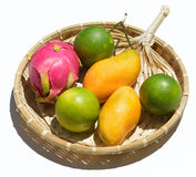 Fresh tropical fruit on a wicker plate on a white background Royalty Free Stock Images