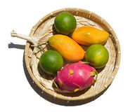 Fresh tropical fruit on a wicker plate on a white background Royalty Free Stock Photo
