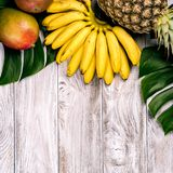 Fresh tropical fruit on wood top view. bananas, pineapple, coconut, mango, lychee, chestnuts. Fresh tropical fruit on wood top view. bananas, pineapple, coconut stock images