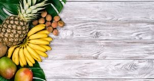 Fresh tropical fruit on wood top view. bananas, pineapple, coconut, mango, lychee, chestnuts. Fresh tropical fruit on wood top view. bananas, pineapple, coconut royalty free stock photo