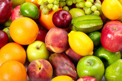 Fresh tropical fruits. Fresh tropical fruits: banana orange apple, grape, peach, lemon, lime. Isolated over white background royalty free stock image