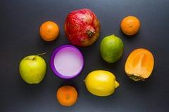 Fresh tropical fruits on black ceramic surface stock photos