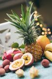Fresh tropical fruits on blue table. Tropical fruits ananas, lychee, bananas, kiwi, passion fruit and others. Toned image Selective focus Royalty Free Stock Photography