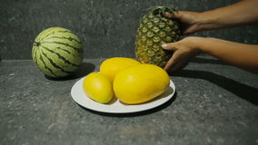 Fresh tropical fruits on plate. Female hand, puts pineapple on a table near a plate with mango stock video