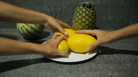 Fresh tropical fruits on plate. Many hands taking mangoes from the white plate stock video footage