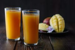 Fresh tropical mango juice on table with mango fruits on background. Royalty Free Stock Image