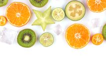 Fresh tropical slices of fruits isolated on white background. Juicy oranges, kiwis, carambolas and ice. royalty free stock images