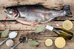 Fresh trout fish with spices on wood. En background Stock Photography