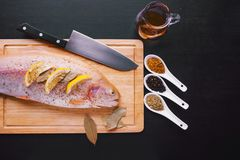 Fresh trout and ingredients to prepare fish dishes on black table. Fresh trout and ingredients to prepare fish dishes on a black table Royalty Free Stock Photography