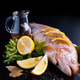 Fresh trout and ingredients to prepare fish dishes on black table. Focus on the decanter of olive oil. Fresh trout and ingredients to prepare fish dishes on a Royalty Free Stock Photo