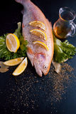 Fresh trout and ingredients to prepare fish dishes on black table, with spices and lemon wedges, top view. Fresh trout and ingredients to prepare fish dishes on Stock Image