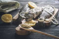Fresh trout with spices on a cutting board. Fresh fish, placed on a wooden cutting board and sprinkled with herbs, slices of lemon and onion, on a rustic black Stock Images