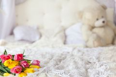 Fresh tulip bouquet on bed. In light tones with white pillows Stock Image