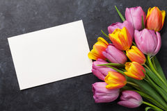 Fresh tulip flowers and greeting card. Fresh colorful tulip flowers and blank greeting card on dark stone table. Top view with copy space Royalty Free Stock Image