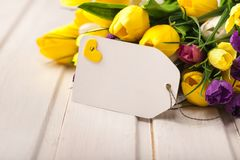 Fresh tulips with blank card on wooden table Stock Images