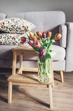 Fresh tulips bouquet in vase are in living room. Cozy home decor. Ation royalty free stock photo