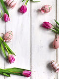 Fresh tulips and decoration eggs frame on white wooden background Royalty Free Stock Photos