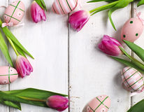 Fresh tulips and decoration eggs frame on white wooden background Stock Photo