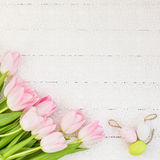 Fresh tulips and decorative Easter eggs on white tablecloth. Top view Stock Photos