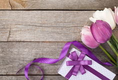 Fresh tulips with gift box. Over wooden table with copy space Stock Image