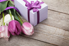 Fresh tulips with gift box. Over wooden table with copy space Royalty Free Stock Image