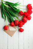 Fresh tulips and greeting card over wooden table background Royalty Free Stock Photos