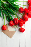 Fresh tulips and greeting card over wooden table background Stock Photo