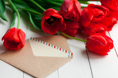 Fresh tulips and letter over wooden table background Stock Images