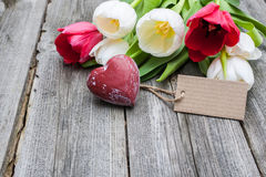 Fresh tulips and red heart with a tag Royalty Free Stock Photography