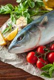 Tuna fish with herbs and vegetables. Fresh tuna fish lying on paper on wooden texture with сherry tomatoes and herbs Royalty Free Stock Photos