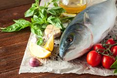 Tuna fish with herbs and vegetables. Fresh tuna head with tomatoes, lemon and spices on wooden background Royalty Free Stock Photography