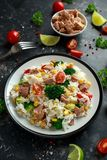 Fresh Tuna rice salad with sweet corn, cherry tomatoes, broccoli, parsley and lime in black bowl royalty free stock photo