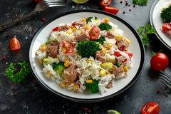 Fresh Tuna rice salad with sweet corn, cherry tomatoes, broccoli, parsley and lime in black bowl stock photo
