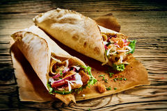 Fresh Turkish doner kebabs in toasted tortillas. Fresh Turkish doner kebabs in toasted tortilla wraps served on brown paper on a rustic wooden table in a close Royalty Free Stock Photography