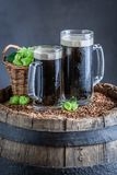 Fresh two pint of dark beer on old barrel. Fresh two pint of dark beer on old wooden barrel royalty free stock photos