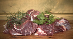 Fresh uncooked beef meat slices over wooden cutting board ready Royalty Free Stock Photo
