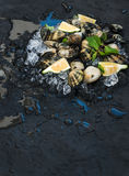 Fresh uncooked clams with lemon, herbs and spices on chipped ice over dark slate stone backdrop, top view, selective. Focus, copy space Royalty Free Stock Image