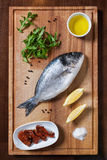 Fresh uncooked dorado fish with ingredients. Fresh uncooked dorado or sea bream fish with lemon, herbs, oil and spices on rustic wooden cutting board, top view Royalty Free Stock Image