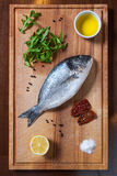 Fresh uncooked dorado fish with ingredients on the wooden board. Fresh uncooked dorado or sea bream fish with tomatoes, lemon, arugula, olive oil and spices on Royalty Free Stock Images