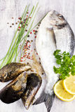Fresh uncooked dorado fish and mussels on light wooden backgroun Stock Photo