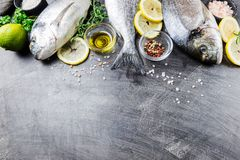 Fresh uncooked dorado. Or sea bream fish with lemon slices, spices and herbs. Mediterranean cuisine. Top view Stock Photo